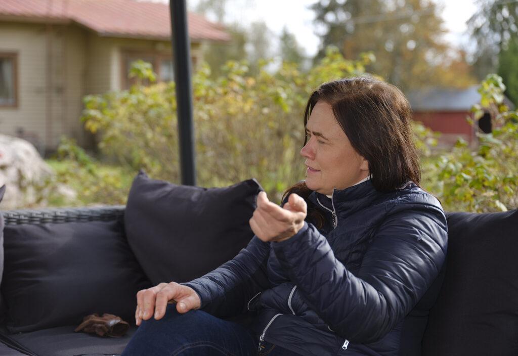 Niina Koivmäki istuu pihalla.