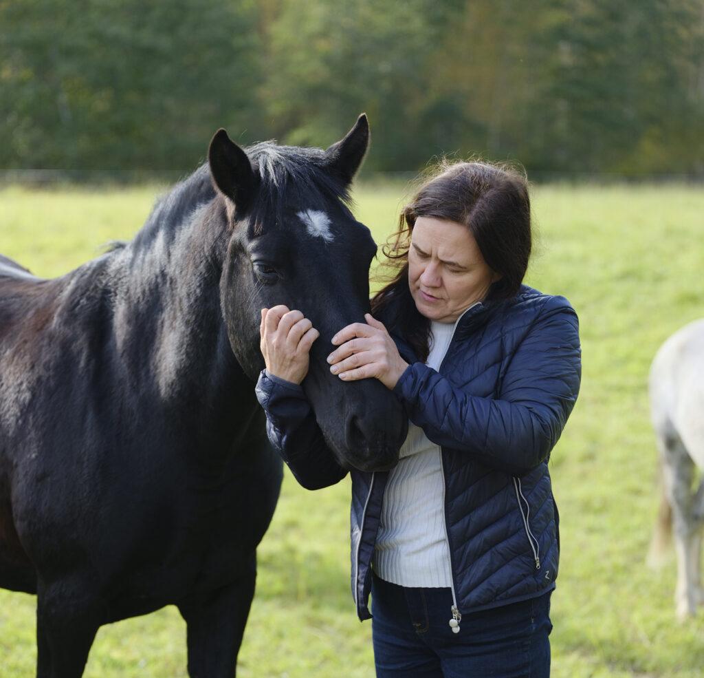 Niina ja musta hevonen laitumella.