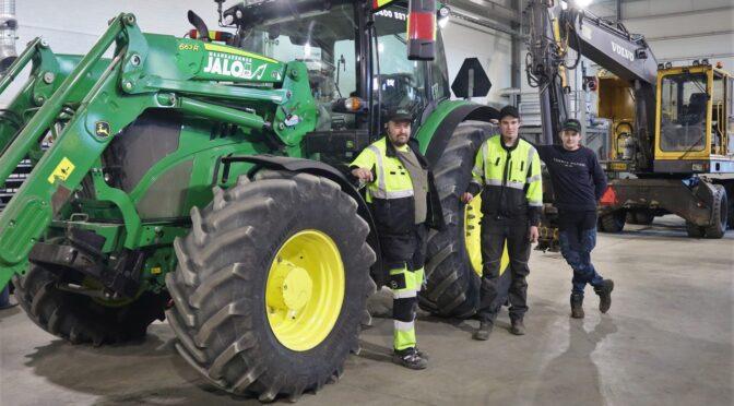 Kolme miestä ison traktorin edessä