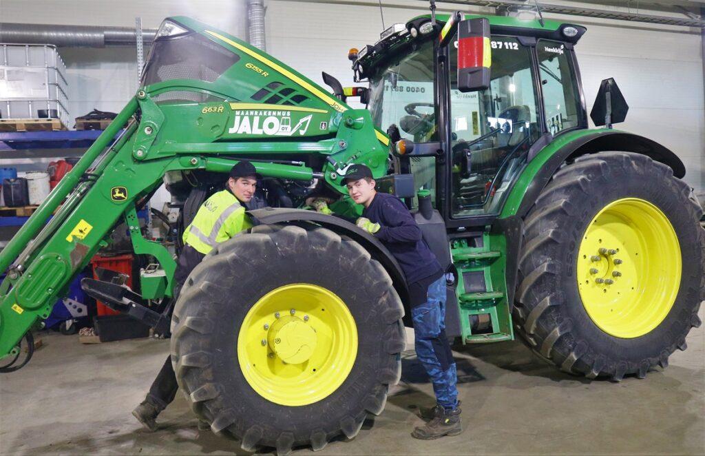 Kaksi nuorta miestä tutkimassa traktoria