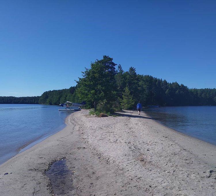 hiekkainen kannas, jolla vesitaso ja kävelevä ihminen