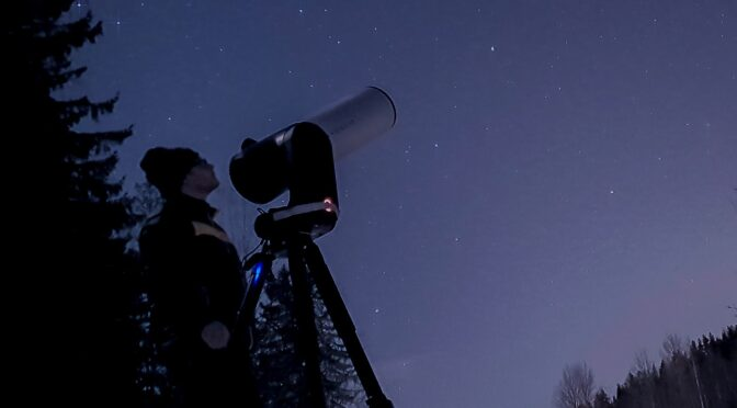 mies katselee kaukoputken läpi yöllä